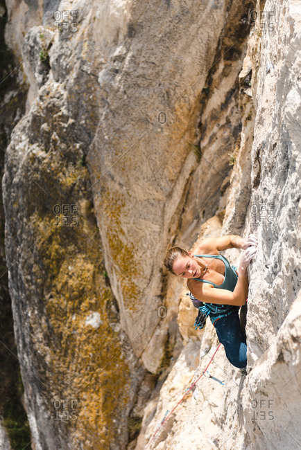 Strong young woman climbing limestone walls in Quiros, Asturias, Spain