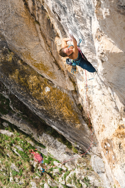 Strong woman rock climber grabbing a ledge in overhanging wall