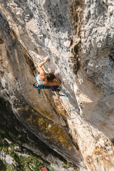 From above view of woman rock climber in limestone wall at sunset