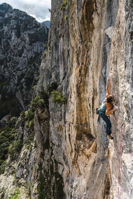 Strong woman rock climber grabbing a ledge in vertical wall
