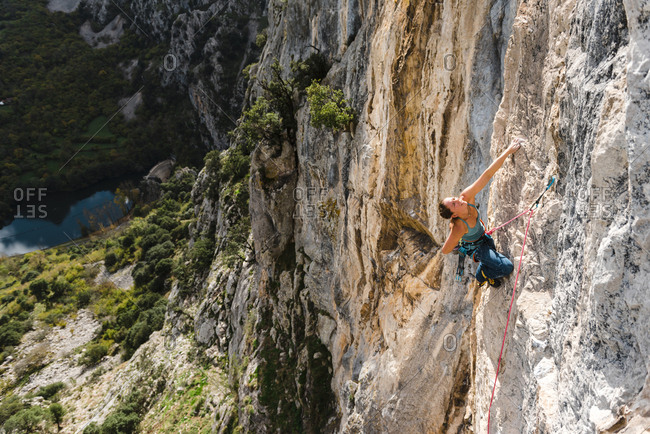 Strong woman rock climber resting from a ledge in vertical wall