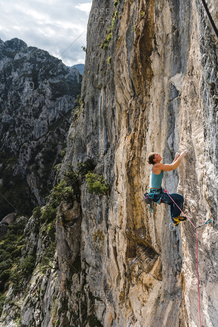 Strong woman rock climber on vertical limestone wall at sunset