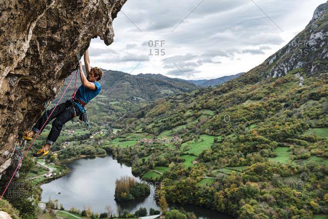 Strong young man climbing limestone wall close to green field and lake