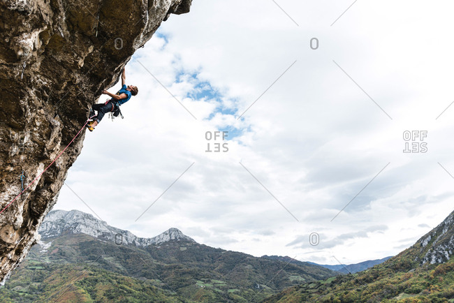 Strong man rock climber grabbing a ledge in overhanging wall