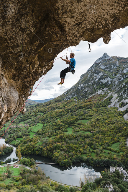 Rock climber descending from limestone wall on cloudy day