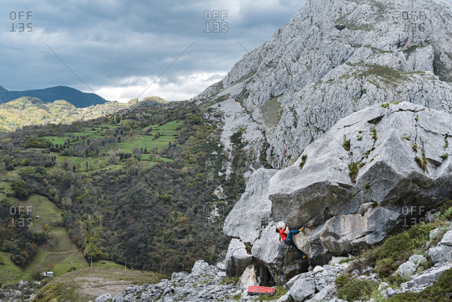 Woman climber trying gray limestone boulder on scenic forest landscape