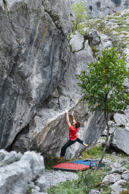 Man climber trying gray limestone boulder on scenic forest landscape