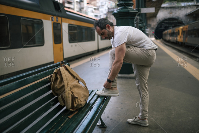 Caucasian man tying his shoe while waiting for a train
