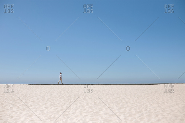 Landscape of sand and sea with man walking in the distance