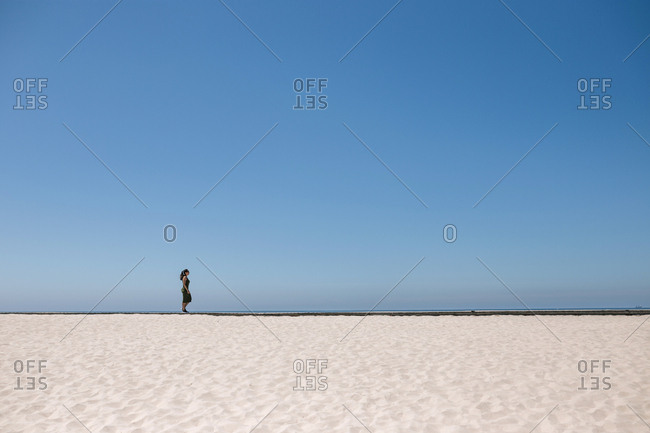 Landscape of sand and sea with woman walking in the distance