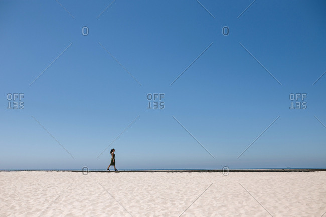 Woman walking in the distance along the coast