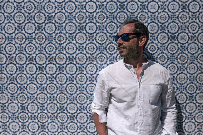 Man with sunglasses standing in front of background of beautiful tiles