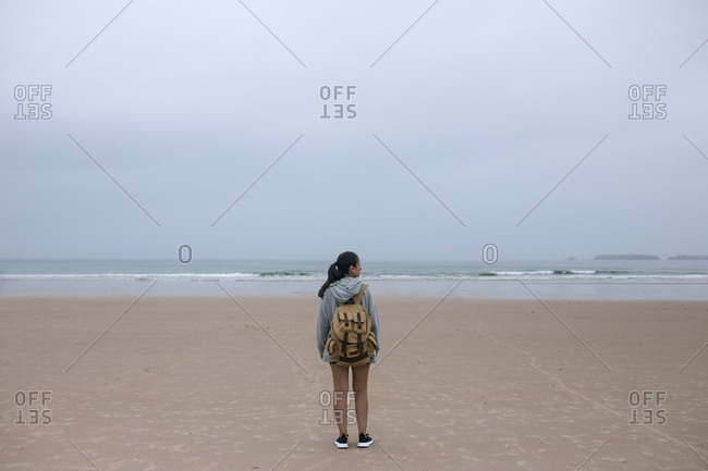 Caucasian woman with backpack on the beach on a cloudy day