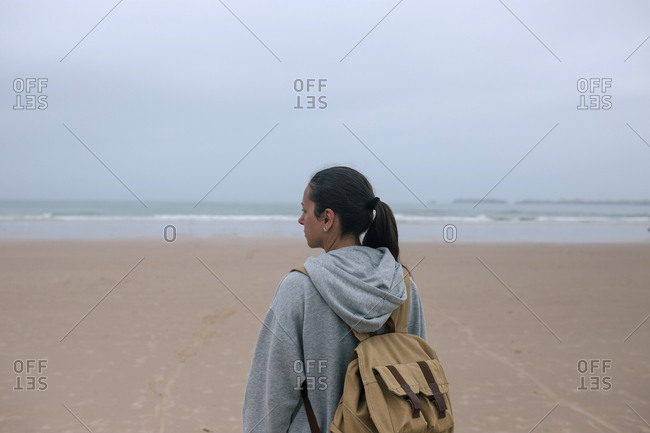 Rear view of Caucasian woman with backpack on the beach on a cloudy day
