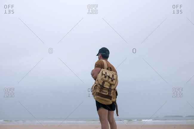 Rear view of man with backpack arrives at a beach on a cloudy day