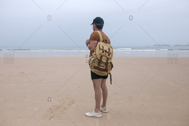Man with backpack arrives at a beach on a cloudy day from behind