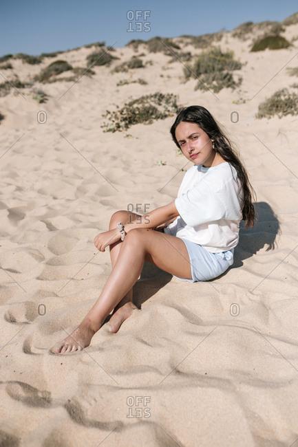 Caucasian teen girl sunbathing on a sandy beach