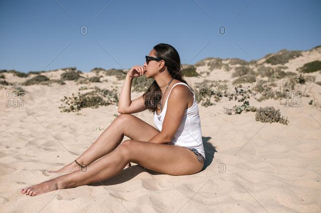 Caucasian teen girl with sunglasses sunbathing on a sandy beach