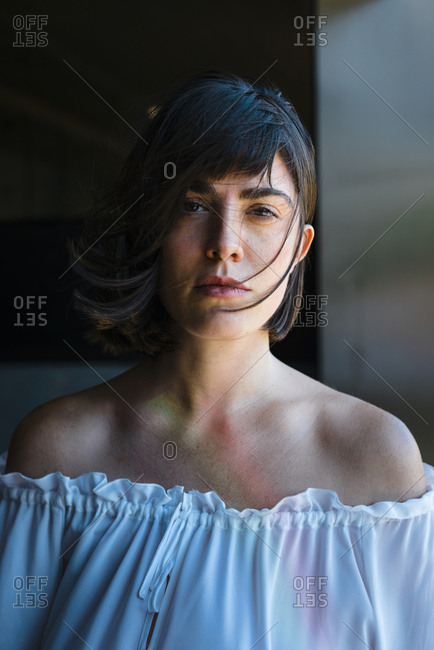 Attractive young brunette woman looking at camera with hair blowing in the wind
