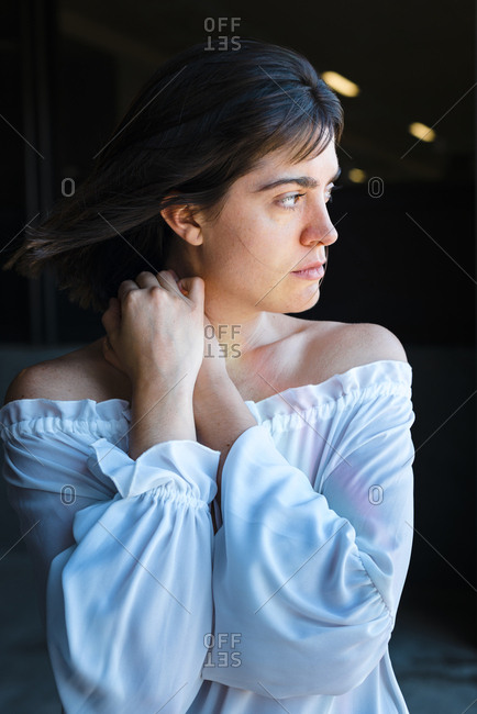 Passionate young brunette woman looking away with hair blowing in the wind