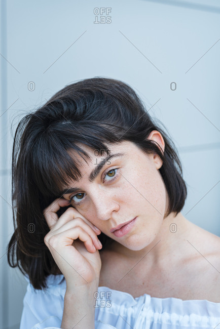 Woman in trendy blouse touching hair and looking at camera against gray wall outside building