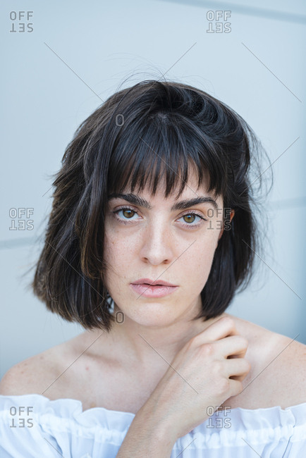 Portrait of a woman in trendy blouse looking at camera in front of gray wall