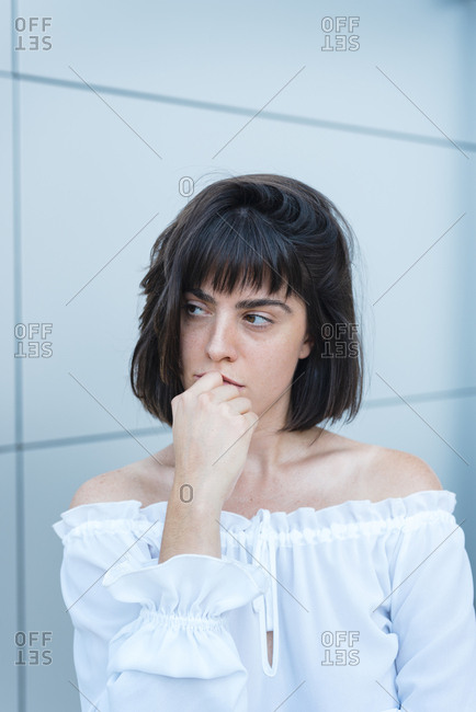 Serious female in trendy blouse looking away in front of gray wall