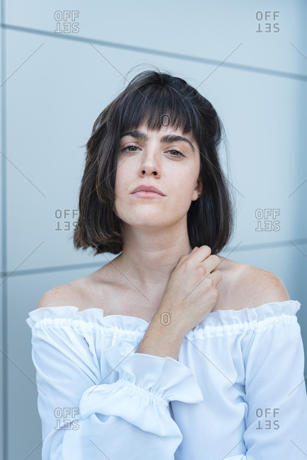 Passionate female in trendy blouse with hand on chest and looking at camera