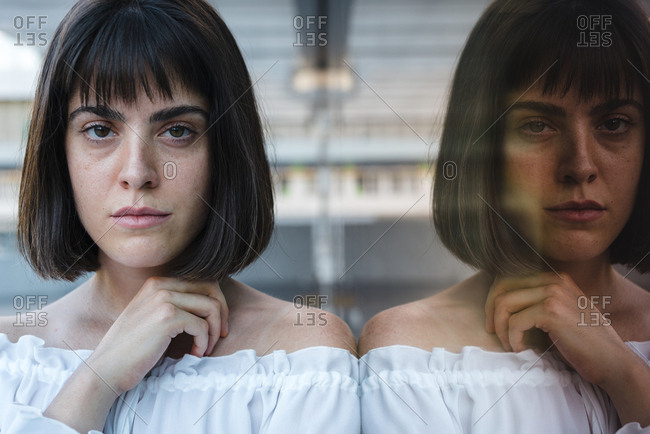 Reflection on glass wall of serious female in trendy blouse looking at camera