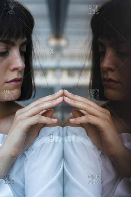 Reflection of female in trendy blouse touching glass with fingertips