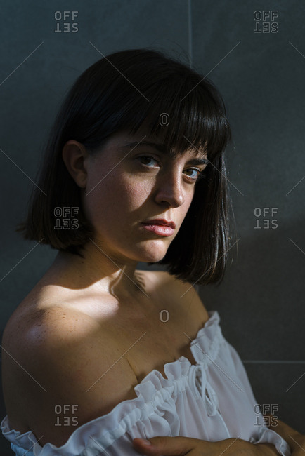 Passionate young lady in white blouse with brunette short hair looking at camera