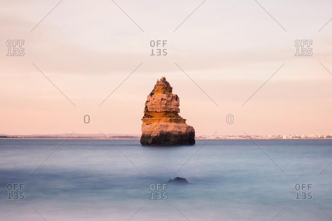 Lonely rock in the ocean at Lagos, Algarve, Portugal. Long exposure