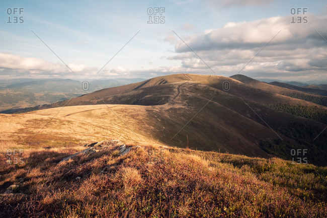 Weathered grass on the mountains hills meadows. Cloudy autumn evening. Panoramic view of mountain landscape