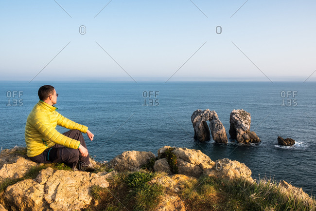 Man in yellow jacket sitting on the cliff with wonderful beautiful ocean view.