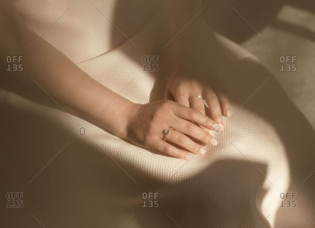 Female hands with rings crossed on lap