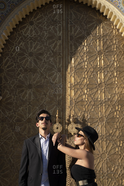 Moroccan man with sunglasses and suit together a beautiful woman