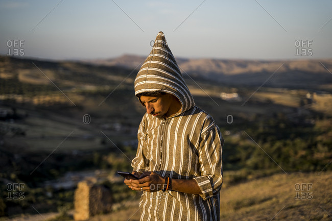 Moroccan man in typical Arabic attire with mobile phone in hand.