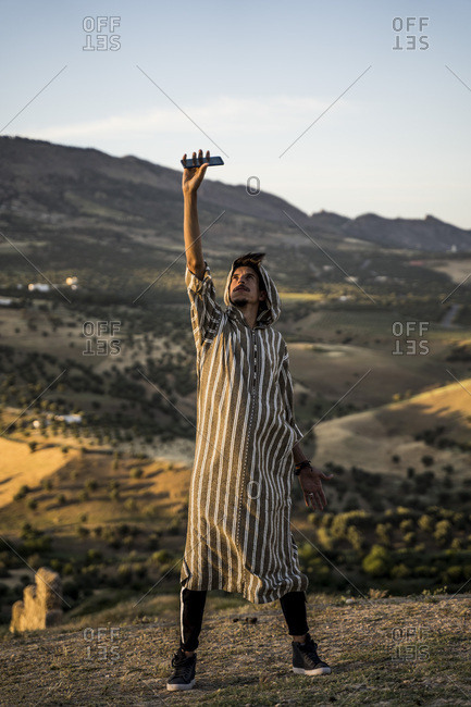 Moroccan man in typical Arabic attire lifting mobile phone up.