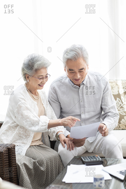 Happy senior Chinese couple reading file in living room