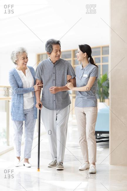 Chinese nursing assistant taking care of senior man
