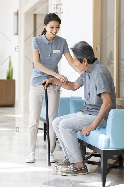 Chinese nursing assistant taking care of senior man