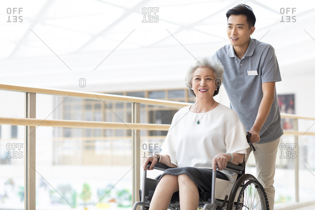 Chinese nursing assistant taking care of senior woman in wheelchair