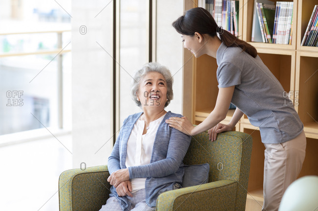 Chinese nursing assistant taking with senior woman in nursing home