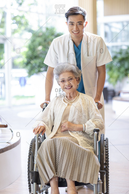Young Chinese doctor taking care of senior woman in wheelchair