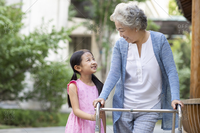 Senior Chinese woman walking with walking frame under granddaughter's assistance