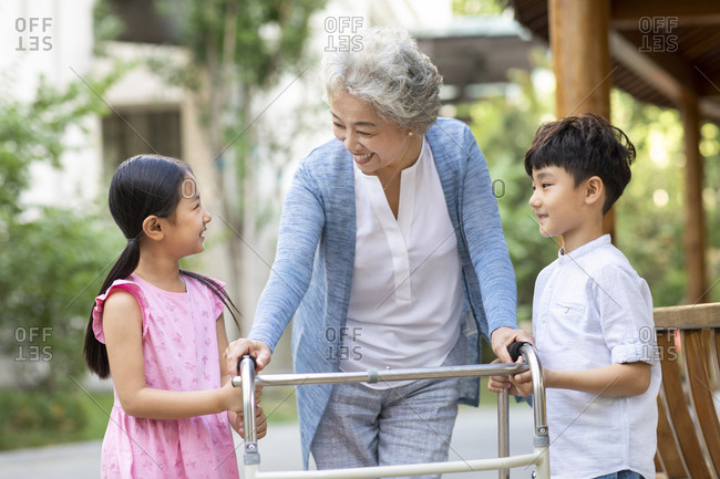 Happy Chinese sibling helping grandma walking with walking frame