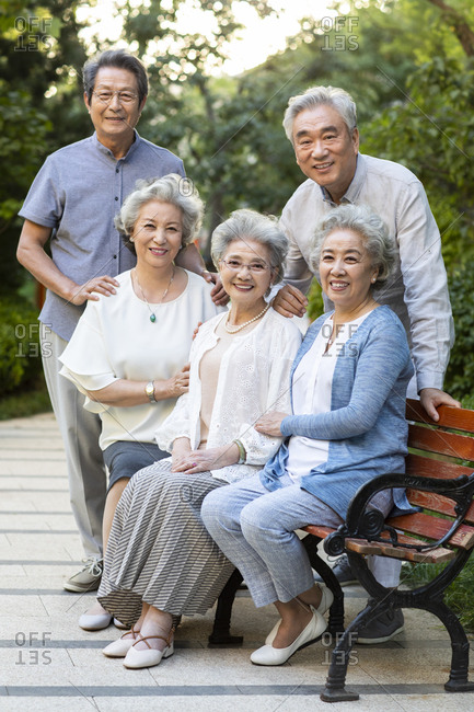 Happy senior Chinese friends relaxing in park