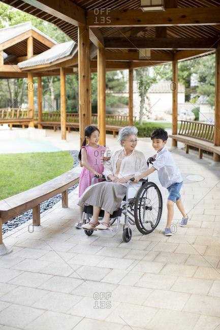 Chinese grandchildren pushing grandmother in wheelchair