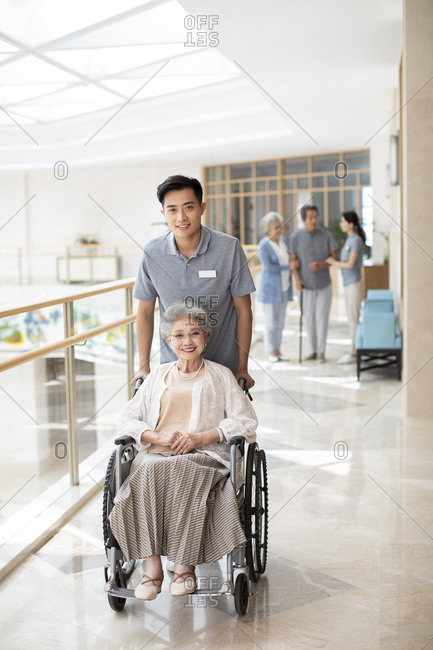 Young Chinese nurse assistant taking care of senior woman in wheelchair