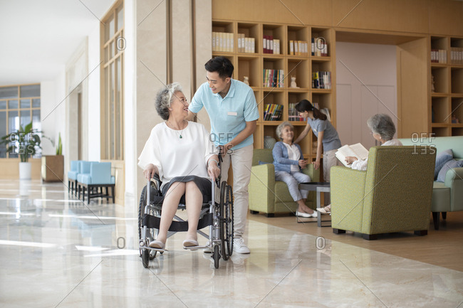 Young Chinese nurse assistant taking care of senior people